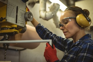 Female worker operating a machine