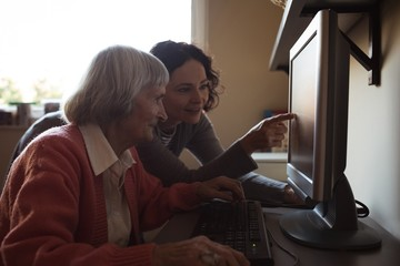 Caretaker assisting senior woman while working on computer