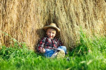 Happy boy in straw hat sitting in haystack