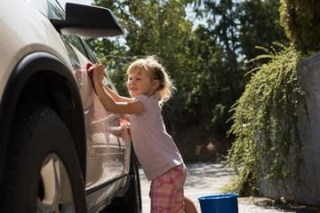Girl washing a car at outside garage