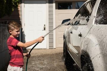 Boy washing a car at outside garage