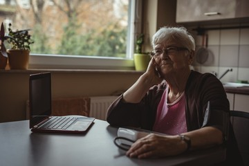 Senior woman sitting with blood pressure machine and a laptop