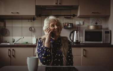 Smiling senior woman talking on the phone in the kitchen