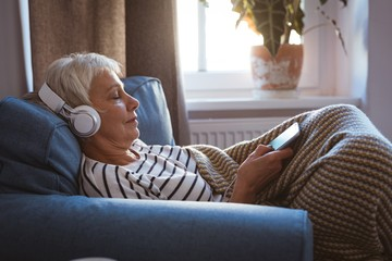 Senior woman listing to music on phone while siting on sofa in