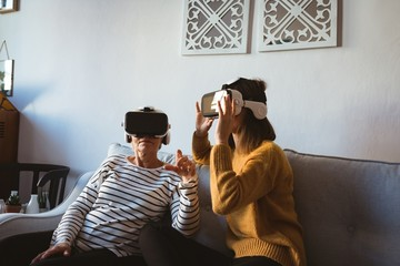 Senior woman and daughter wearing a virtual reality headset
