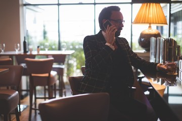 Businessman talking on mobile phone while having whisky
