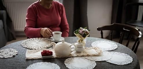 Senior woman having cup of tea in living room