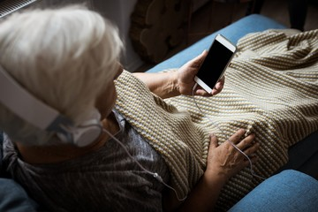 Senior woman listening to music on headphones while using mobile