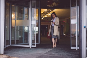 Businesswoman using mobile phone while walking out of the hotel