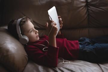 Boy using digital tablet with headphones in living room