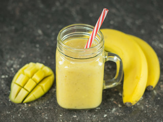 A smoothie of mango, banana, honey and cereal on a black stone table. A bowl of honey.