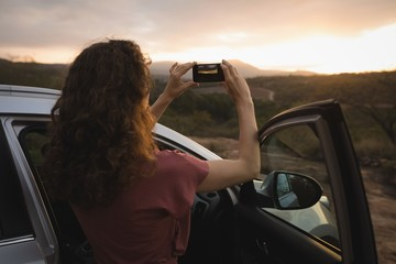 Woman taking picture of nature with mobile phone