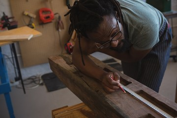 Carpenter measuring wooden plank with tape measure