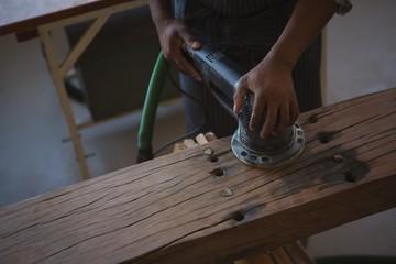 Mid section of carpenter leveling wood with polishing machine