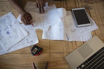 Carpenter drawing on paper in workshop