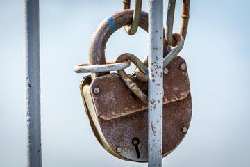 Beautiful closed padlock hanging on the iron fence