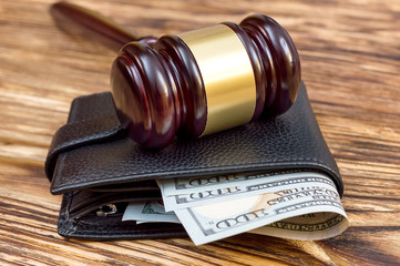 Gavel and wallet with money on the table.