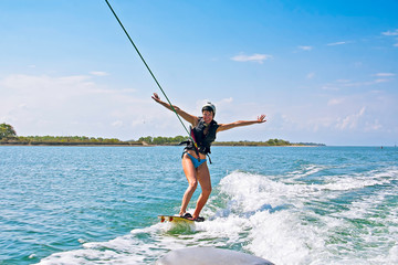 A woman wake boarding on tropical island. Beautiful tropical vacation on Bali.