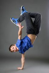 boy standing on his hand in studio