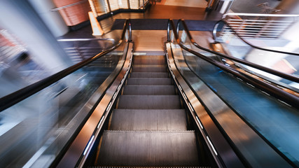 Escalator in motion. diminishing moving escalator in office center