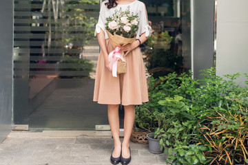 Cropped image of woman standing in flower shop and holding bouquet of flowers
