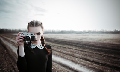 Serious young girl photographing by the old film camera. Outdoor portrait in field