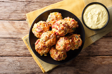 Freshly baked sausage balls with cheese cheddar on a plate and mustard sauce close-up. horizontal top view