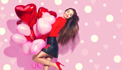 Valentine's Day. Beauty girl with colorful air balloons having fun over pink background