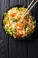 Vietnamese chicken salad with rice noodles, carrots and herbs macro. Vertical top view