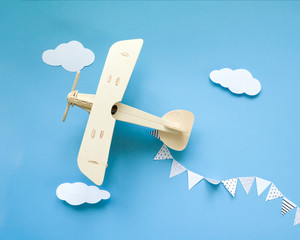wooden children's plane on a blue background, white clouds, flags