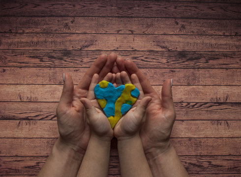 Woman's and child's hands holding a heart of blue and yellow color of world Down syndrome Day.