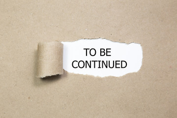 The text to be continued appearing behind torn paper