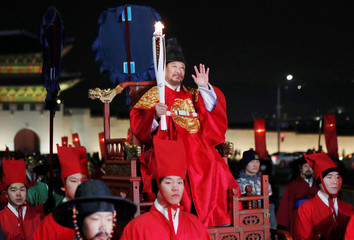 A torchbearer wearing a traditional costume carries the Olympic torch in Seoul