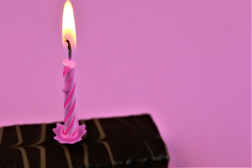 An concept Image of one candle on cake - with pink Background and copy space