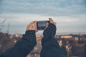 Girl with the phone takes pictures of the city's panorama