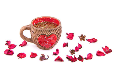 Valentine's Day still life. Clay cup with a red heart and rose petals on white background