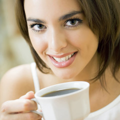 Young happy smiling woman drinking coffee, at home