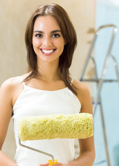 Woman with paint roller in new house