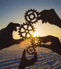 Four hands collect the gear from the gears of the details of the puzzles. against the background of sunlight. Concept business idea. Teamwork