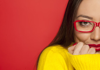 half portrait of beautiful woman with red glasses on red background