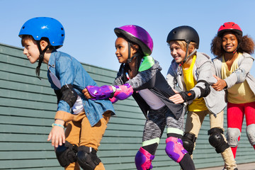 Happy children rollerblading together outdoors