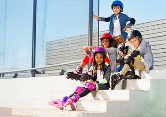 Kids in roller skates sitting on steps of stadium