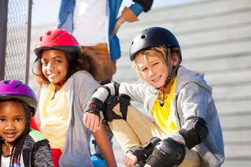 Preteen boy in roller helmet sitting at stadium