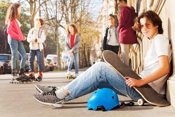 Boy with skateboard and helmet sitting on sidewalk