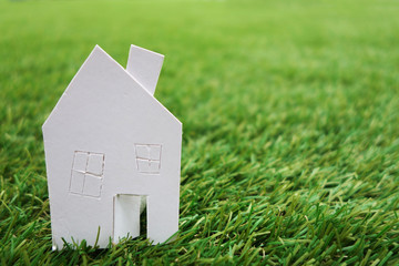 Paper house against on green grass
