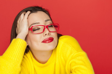 beautiful satisfied and careless woman with red glasses on red background