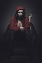 Little red riding hood with whip sitting on sofa