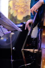 A musician on a double bass playing live music in a restaurant in the orchestra