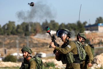 An Israeli soldier fires tear gas at Palestinian demonstrators during clashes at a protest calling for the release of Palestinian prisoners from Israeli jails near Ramallah