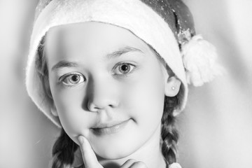 Baby in hat of Santa Claus thinking with finger on cheek